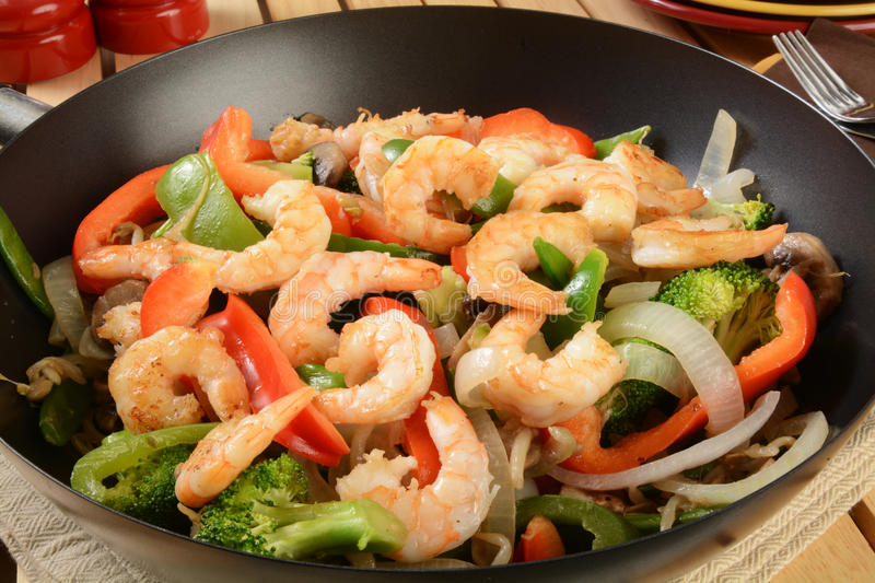 Shrimp stir fry in a wok. Closeup of shrimp stir fry in a wok with serving plates royalty free stock image