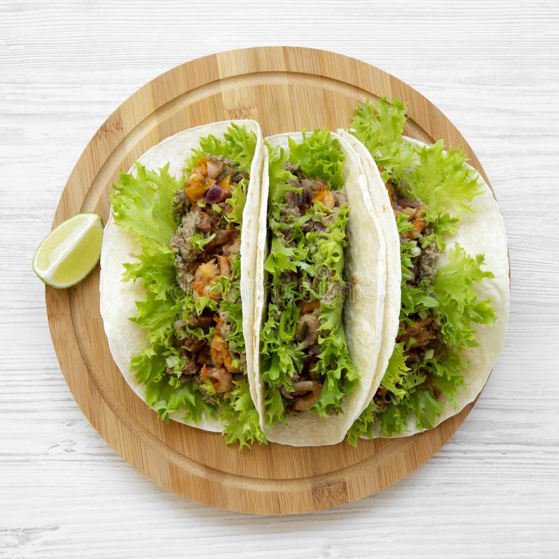 Shrimp tacos on round bamboo board on white wooden table, overhead view. Mexican cuisine. Close-up. Flat lay, from above royalty free stock image