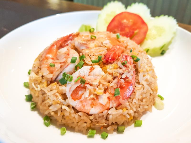 Shrimps fat fried rice garnish with slice cucumbers and tomato on top with shrimps royalty free stock image