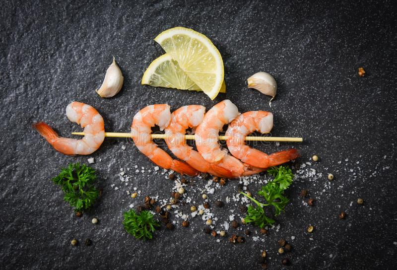 Shrimps prawns in skewer sticks seafood cooked with herbs and spices on dark background stock photography