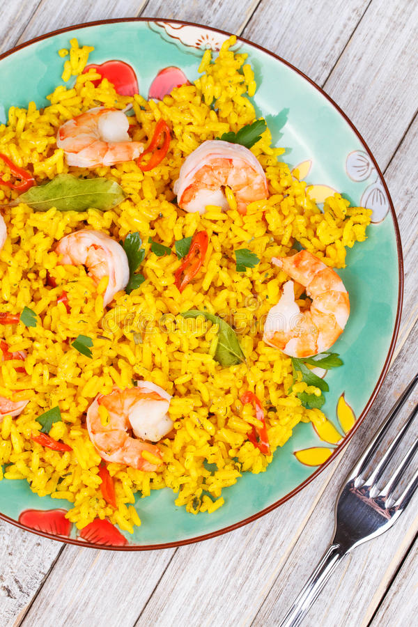 Shrimps Risotto garnished with fresh parsley and red chili pepper. Plate of Shrimps Risotto garnished with fresh parsley and red chili pepper royalty free stock photo