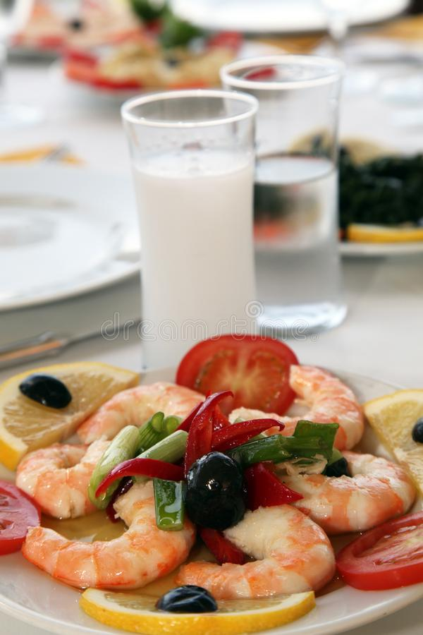 Shrimps with tomatoes and raki. On the restaurant table stock image