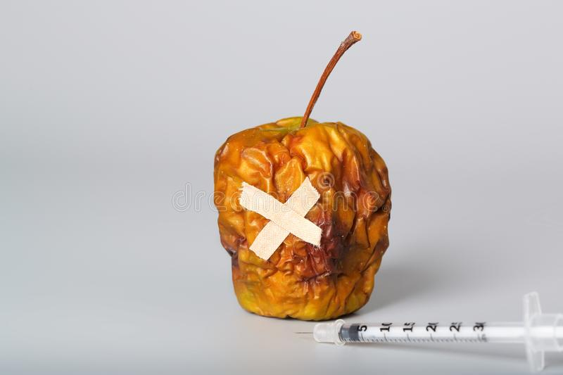 Shrivelled apple and insulin ultra thin syringe on a gray surface. Closeup royalty free stock photo