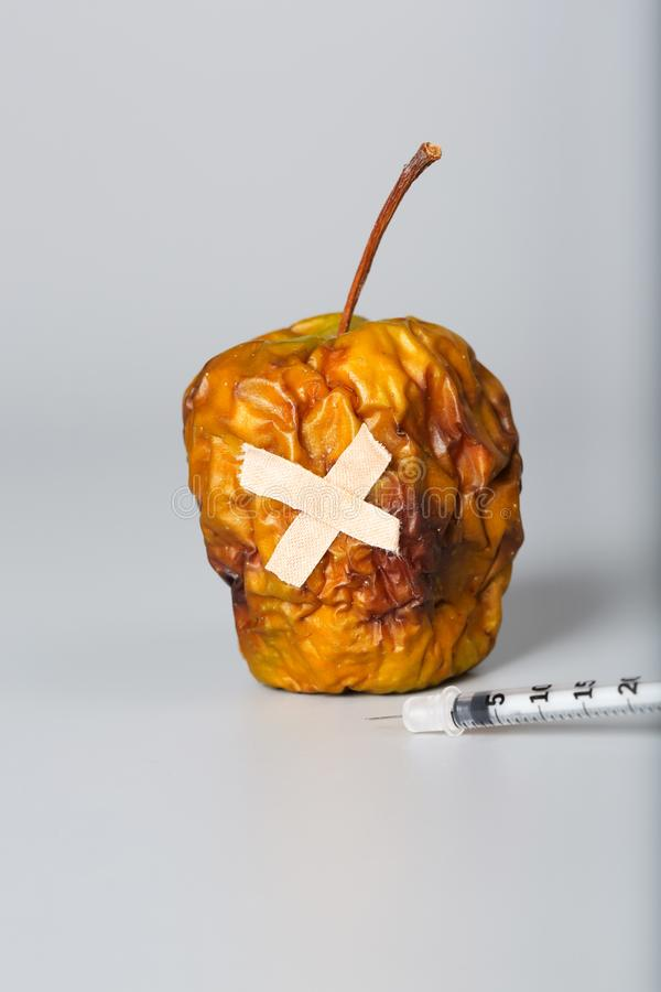 Shrivelled apple and insulin ultra thin syringe on a gray surface. Closeup stock photos