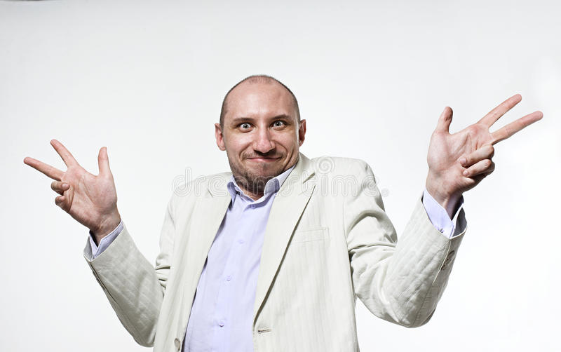 Shrugging man in doubt and surprise doing shrug showing open palms. Businessman portrait over light grey background royalty free stock photo