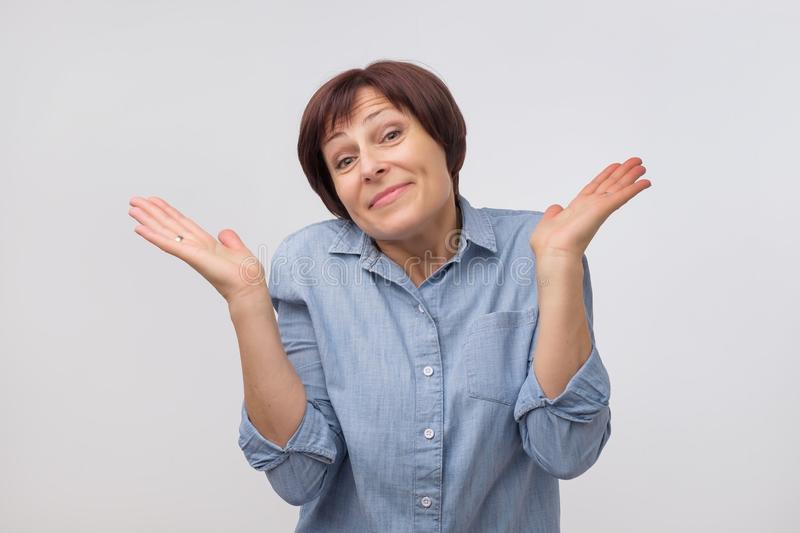 Shrugging mature woman in doubt looking at camera royalty free stock photos