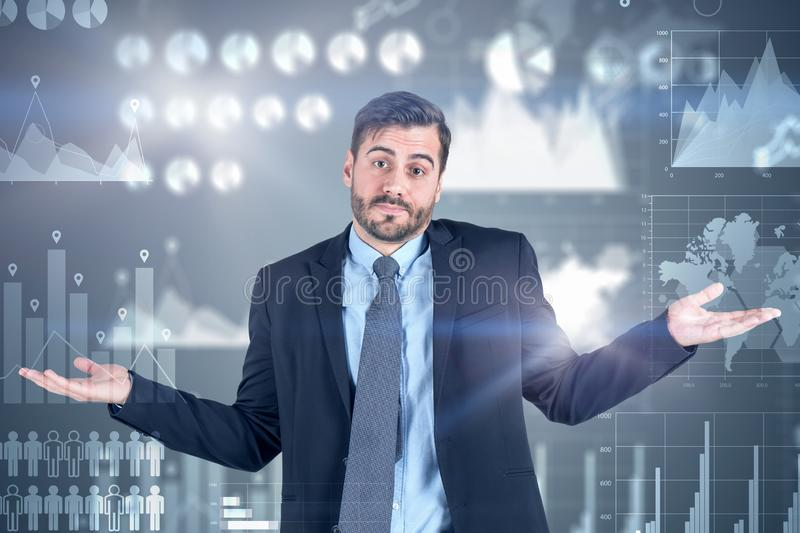 Shrugging shoulders businessman, dark infographics. Portrait of young bearded businessman in suit shrugging his shoulders standing near dark gray wall with royalty free stock image