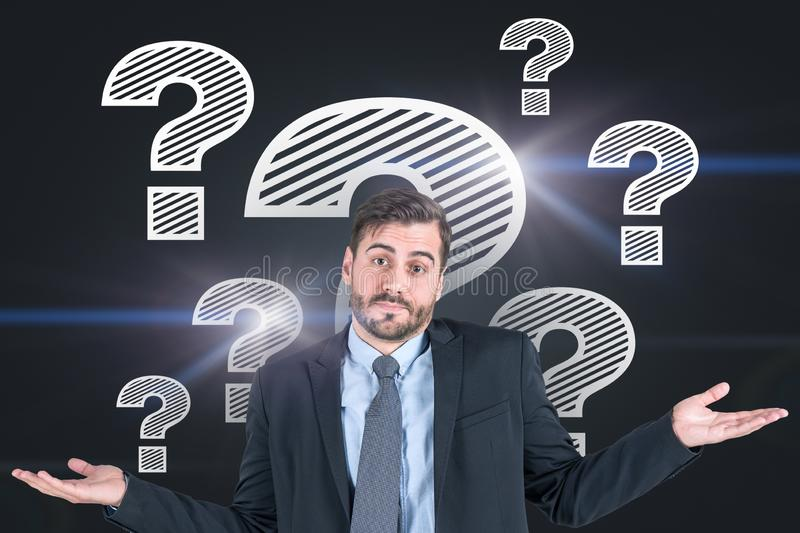 Shrugging shoulders man, question marks. Portrait of young bearded businessman in suit shrugging his shoulders standing near black wall with question marks on it stock photo
