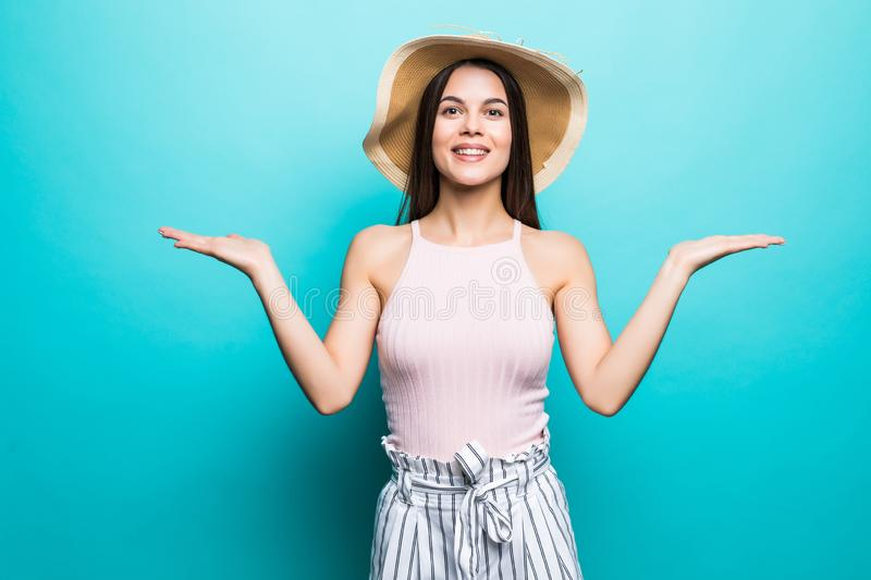 Shrugging woman in doubt doing shrug showing open palms, gesturing, look to side on blue background royalty free stock photography