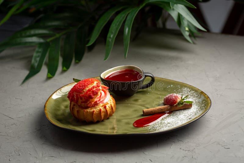 Shu da morango com molho doce em um fundo cinzento foto de stock royalty free