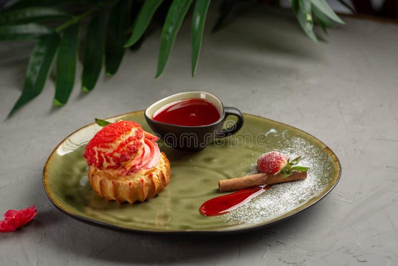 Shu da morango com molho doce em um fundo cinzento foto de stock