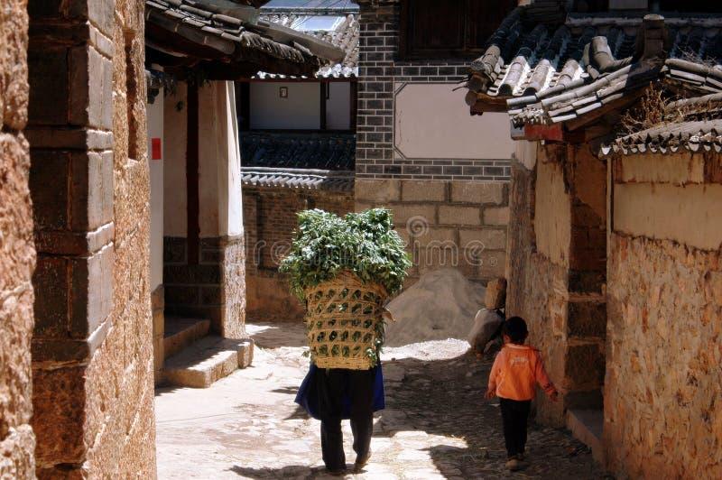 Shu il, Chine : Femme avec le panier de paille photos stock