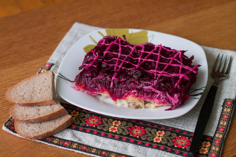 Shuba. Dressed herring (Ukrainian: Shuba) is a layered salad composed of diced salted herring covered with layers of grated boiled vegetables (potatoes, carrots stock photography