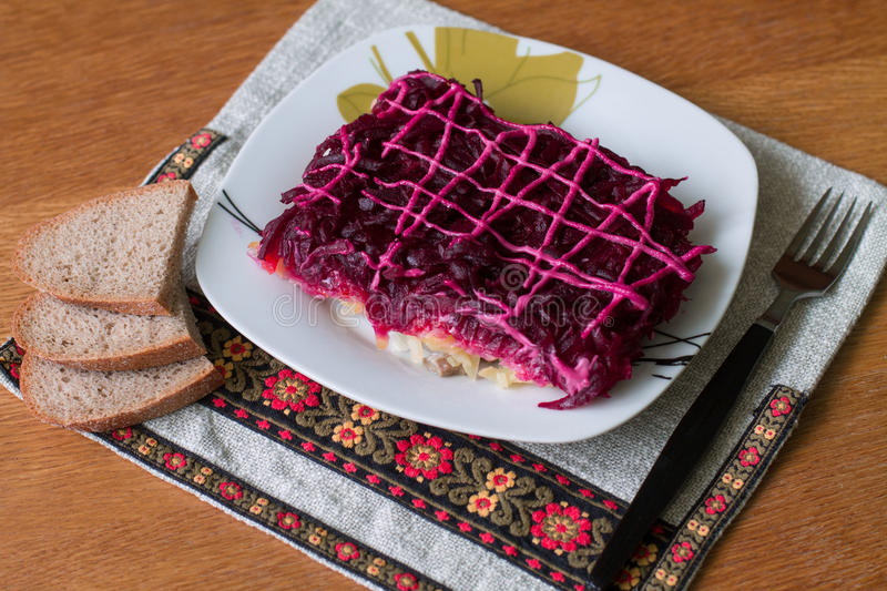 Shuba. Dressed herring (Ukrainian: Shuba) is a layered salad composed of diced salted herring covered with layers of grated boiled vegetables (potatoes, carrots stock image