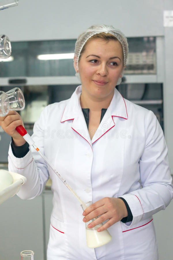 SHUCHIN, БЕЛАРУСЬ - 26-ОЕ ЯНВАРЯ 2015 Молодая женщина в химической лаборатории делая микробиологическую и химическую проверку кач стоковые фото