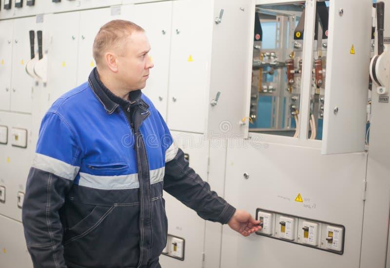 SHUCHIN, БЕЛАРУСЬ - 26-ОЕ ЯНВАРЯ 2015 Профессиональный электрик устанавливая компоненты в электрический экран стоковые изображения