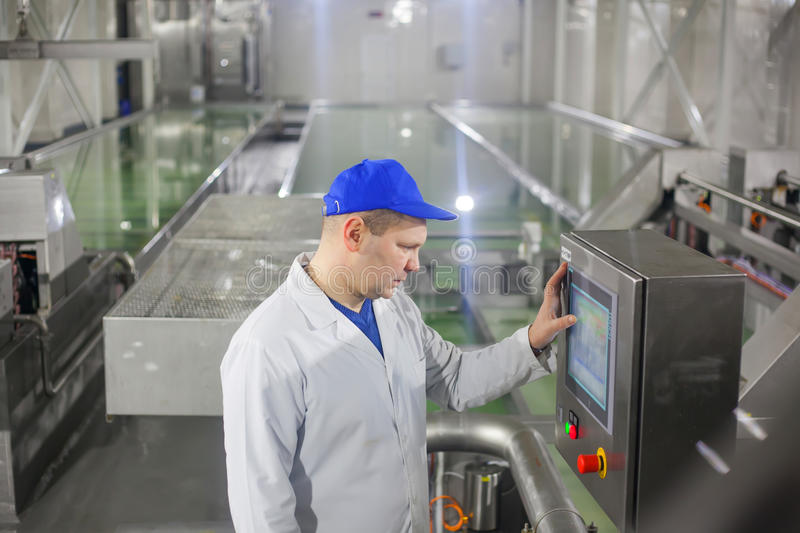 SHUCHIN, BELARUS - JANUARY 26, 2015. man worker operating production line at the cheese factory stock photos