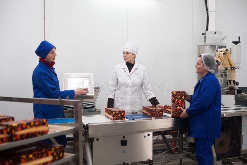 SHUCHIN BIAŁORUŚ, STYCZEŃ, - 26, 2015 Kobiety angażowali w pakować ser na serowej fabryce obraz royalty free