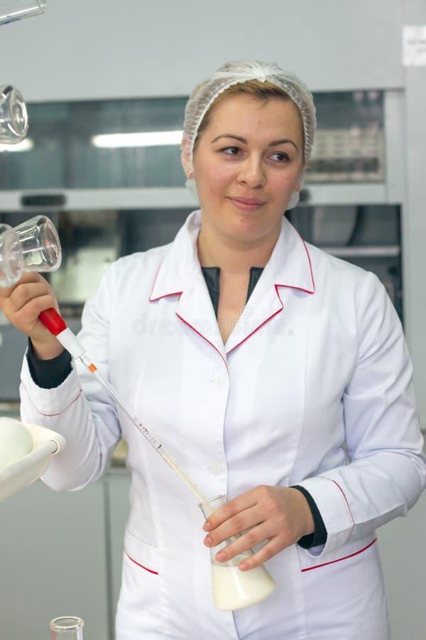 SHUCHIN BIAŁORUŚ, STYCZEŃ, - 26, 2015 Młoda kobieta w chemicznym lab robi mikrobiologicznej i chemicznej kontrola jakości mleko zdjęcia stock