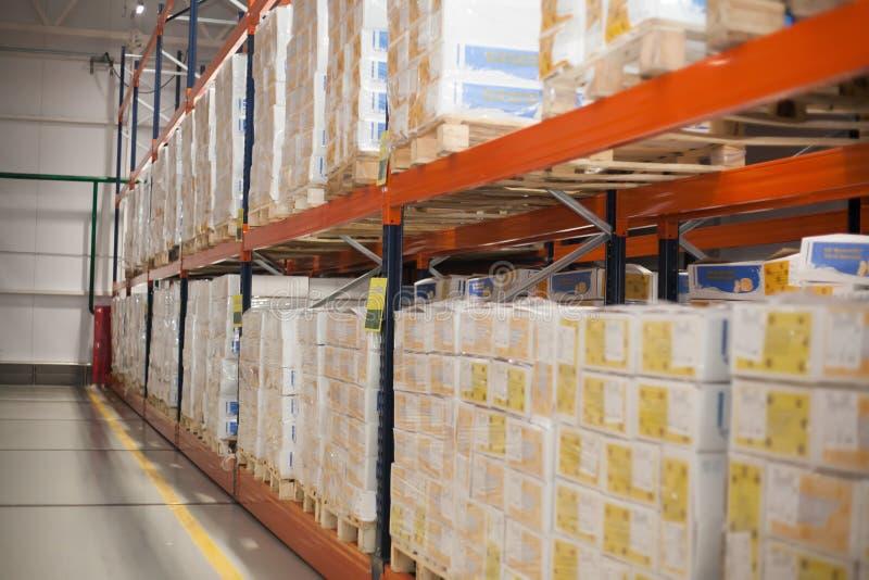 SHUCHIN, BIELORRUSIA - 26 DE ENERO DE 2015 Cajas del cargo que almacenan en los estantes del almacén imagen de archivo