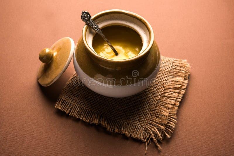 Shuddha Desi Ghee or clarified butter. Desi Ghee or clarified butter in glass or Copper container or ceramic jar with spoon, selective focus stock image