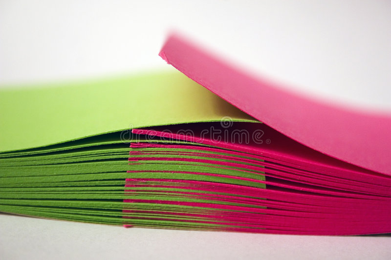 Shuffled Notes. Shuffled pink and green pieces of paper royalty free stock photo