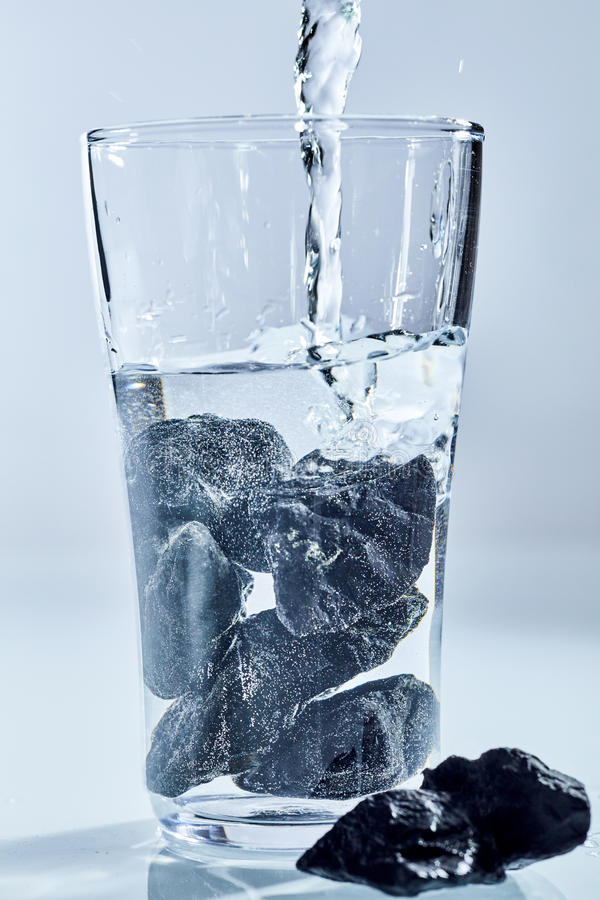 Shungite stones being used to purify water. Shungite stones, a rock with an extremely high carbon content from Karelia, Russia, being used to purify water in a royalty free stock photography