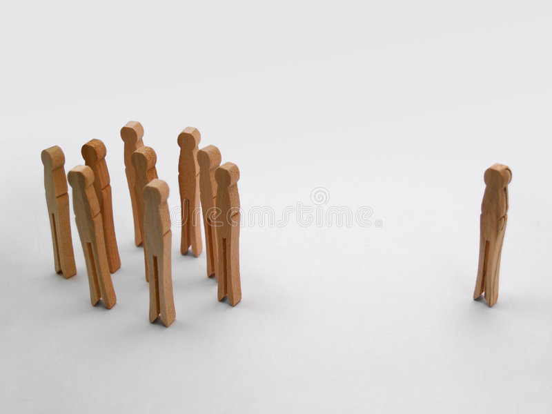 Shunned. One clothespin standing alone outside the group royalty free stock images