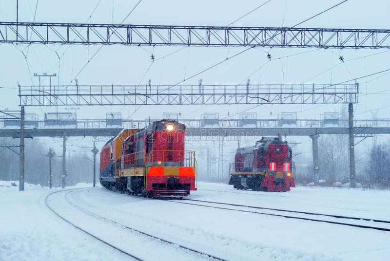 Shunting diesel locomotives during snowfall. Two shunting diesel locomotives on a branch line in winter during a snowfall stock photography