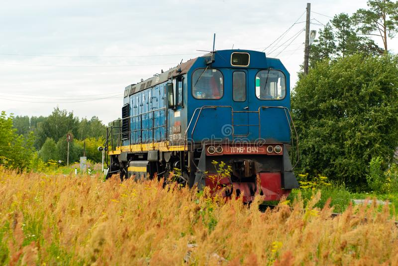 Shunting locomotive on a railway line among the forest and field. Yekaterinburg, Russia - July 10, 2019: shunting locomotive TGM6 on a railway line among the royalty free stock image