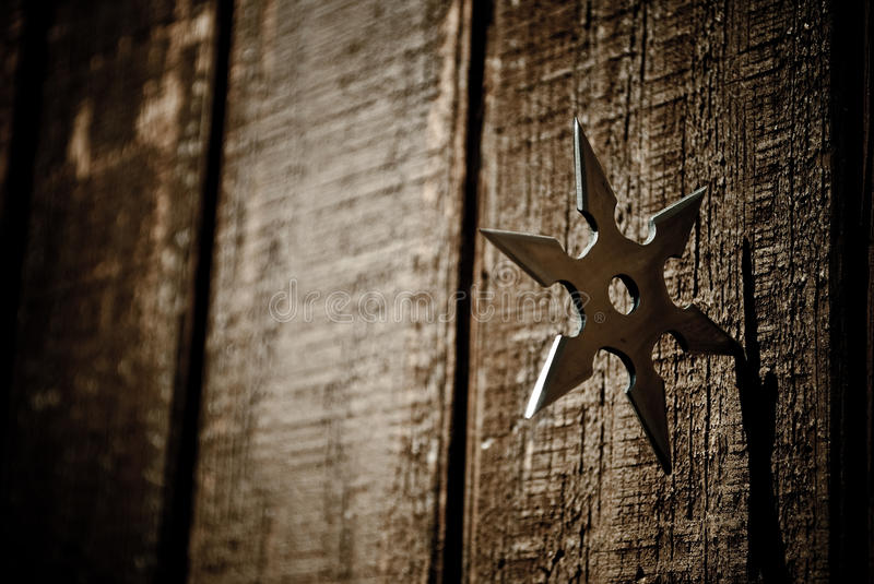Shuriken star embedded in wood. Traditional Japanese Ninja Shuriken throwing star embedded in wood stock photography