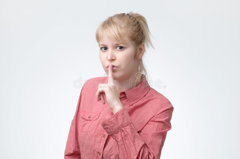 Ovely blonde female asks to keep secret information confidential, dressed in pink shirt. Shush, be silent concept. Lovely blonde female asks to keep secret stock photos