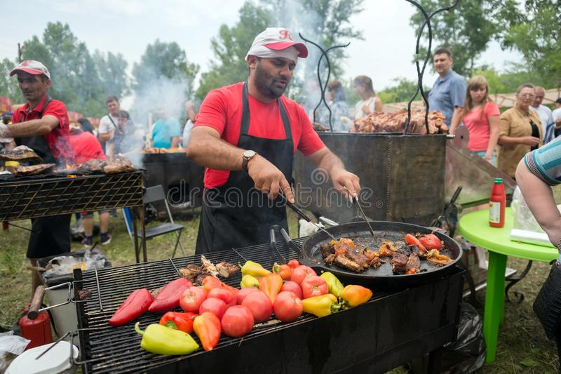 Cook prepares meal on the grill for sale in a summer cafe at the annual Intl festival `World of Siberia`FestMirSibiri. stock images