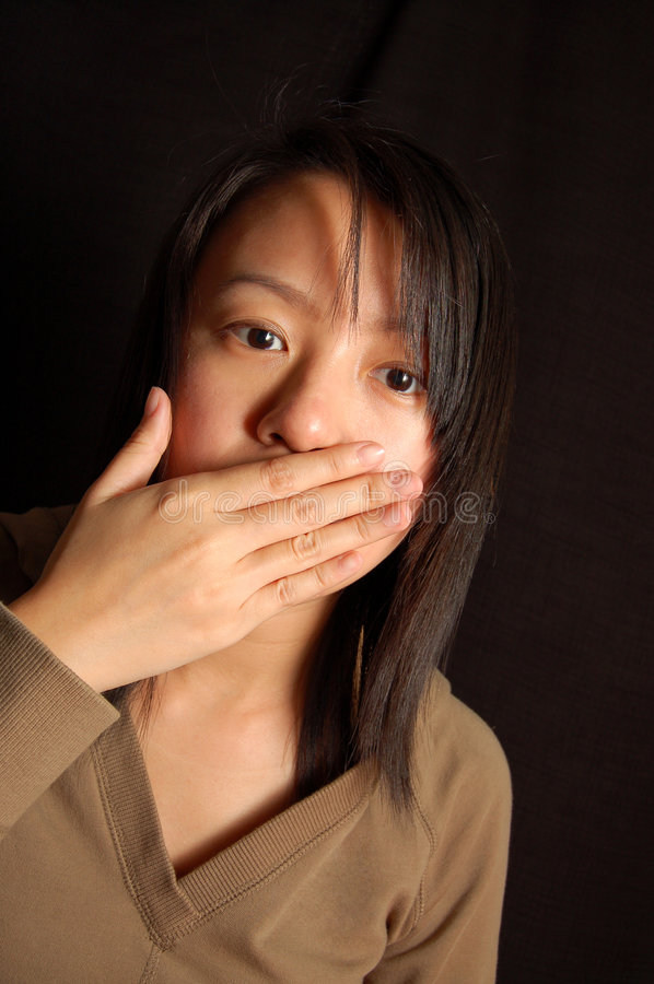 Shut up. An asian lady with hand cover her mouth royalty free stock photo