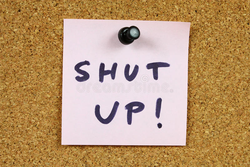 Shut up. Pink sticky note pinned to an office notice board. Shut up - frustration, noise and moderately offensive silence request royalty free stock photography