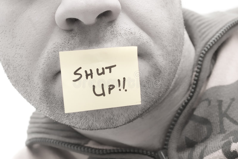 Shut up. A post it in a man mouth saying Shut Up stock photo