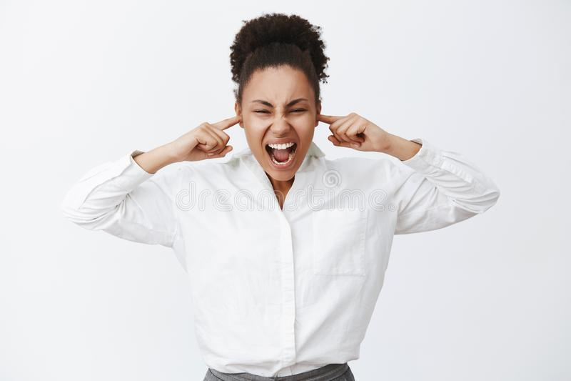 Shut up everybody. Portrait of intense distressed female african-american businesswoman in white shirt, shouting while. Closing ears with fingers, being and royalty free stock photos