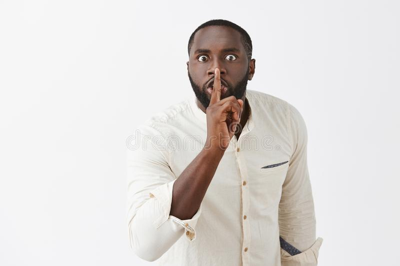 Shut up and listen. angry african american guy with beard in white shirt, bending towards camera with scary. Expression, saying shh while showing shush gesture stock photo