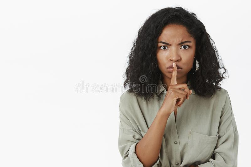 Shut up and listen. Portrait of intense displeased serious-looking african american woman shushing at camera with royalty free stock photos