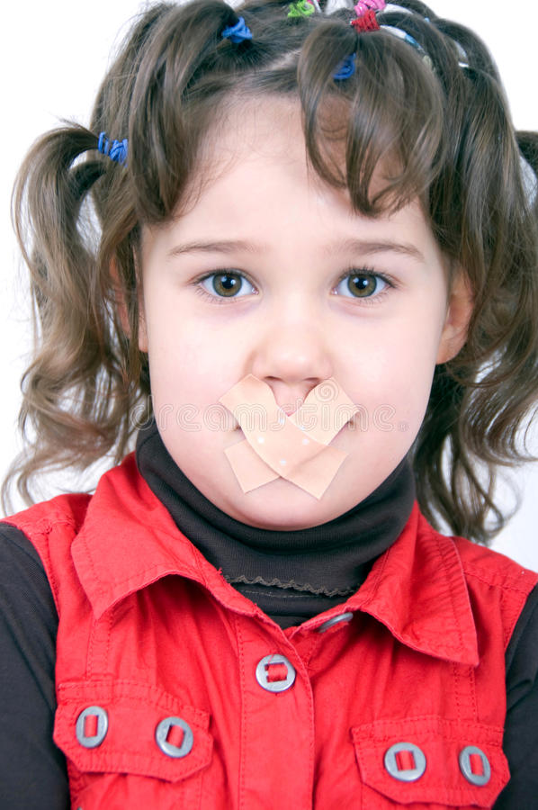 Shut up. Little girl with funny hairstyle has a plaster on the mouth because to be quiet royalty free stock images