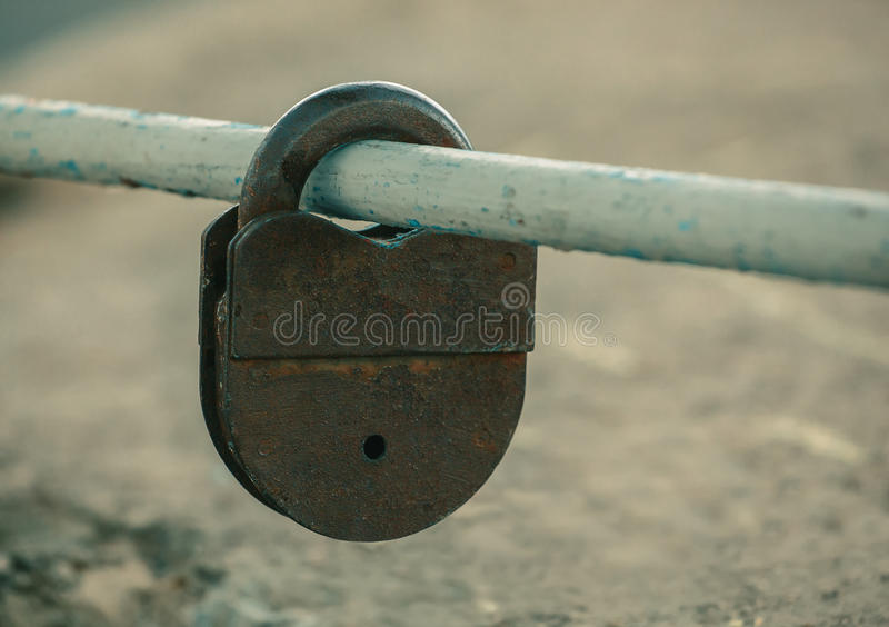 Shut up, old, worn, rusty, shabby padlock hanging on painted, worn, cut, pipe. Outdoors royalty free stock images