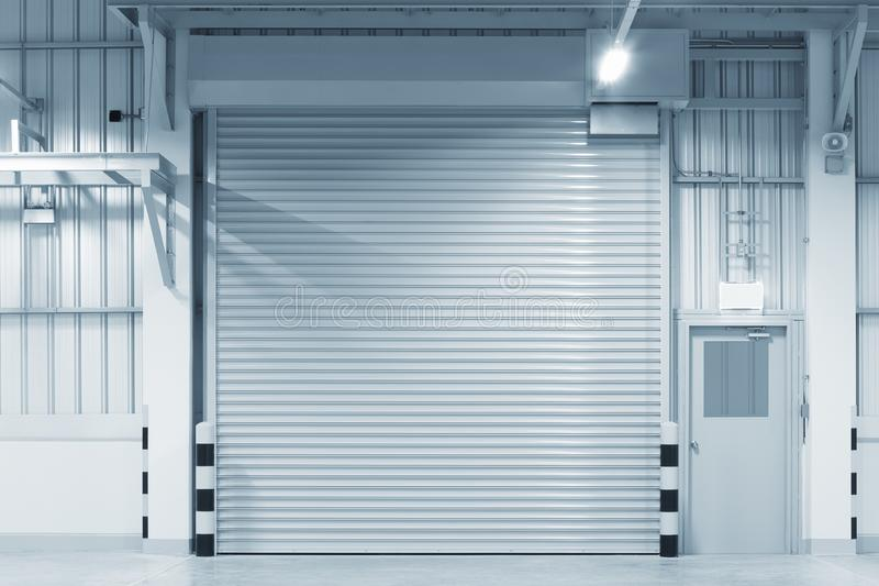 Shutter door factory. Roller shutter door and concrete floor outside factory building for industry background royalty free stock images