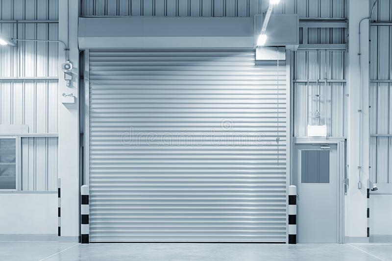 Shutter door factory. Roller shutter door and concrete floor outside factory building for industry background royalty free stock photography