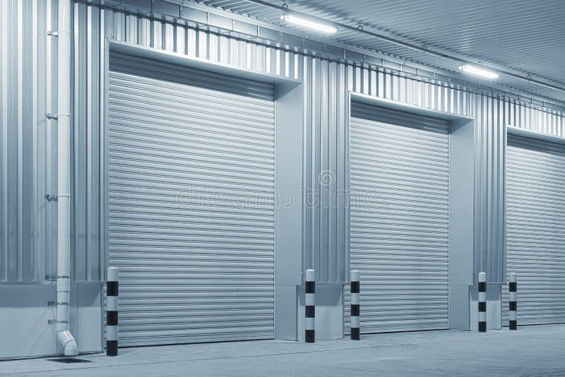 Shutter door night. Shutter door or roller door and concrete floor outside factory building for industrial background royalty free stock image