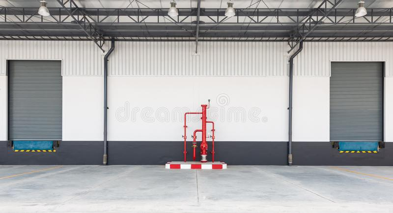 Shutter door or roller door and concrete floor outside factory for loading and unloading goods in industry. Industrial concept stock image
