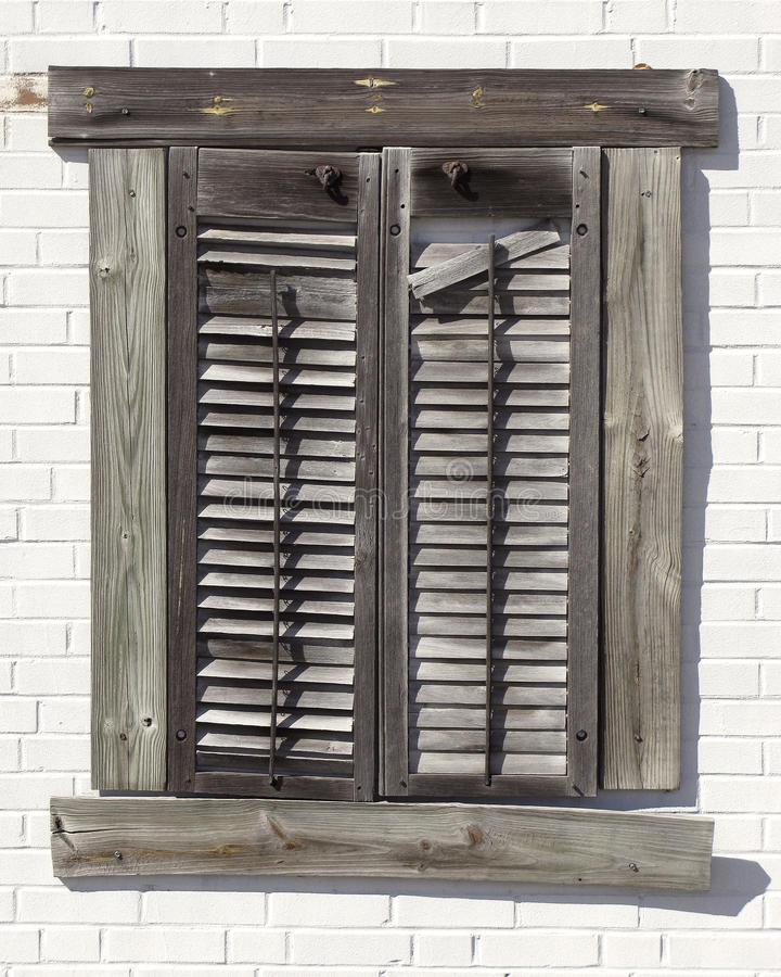 Shuttered Wall. A distressed old wooden shutters nailed to a white painted brick wall stock photos