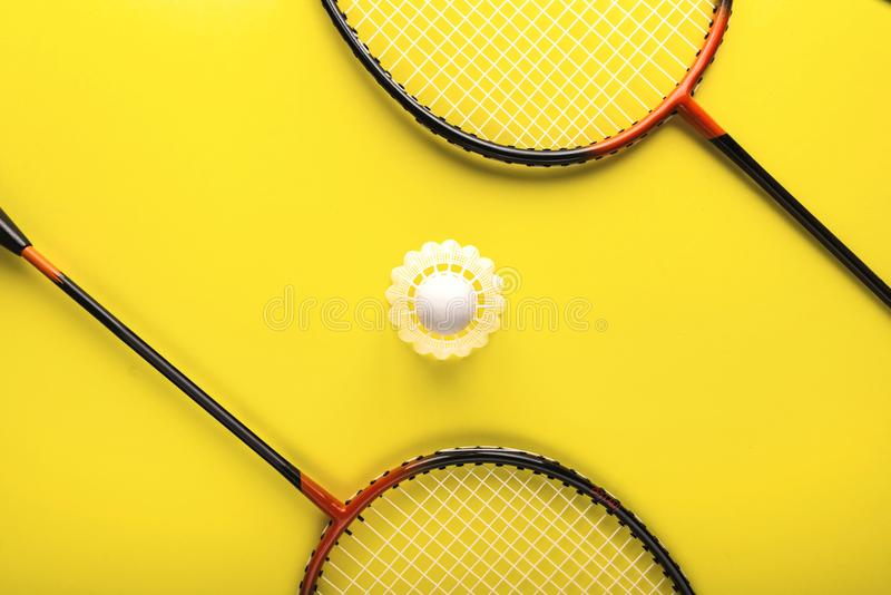 Shuttlecock和球拍打的羽毛球在黄色背景 简单派 razlecheny概念的夏天 库存图片