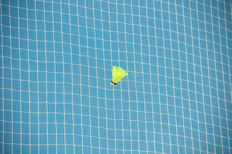 Shuttlecock in a grid badminton. Bright yellow shuttlecock in white net on blue background, badminton close-up stock photo