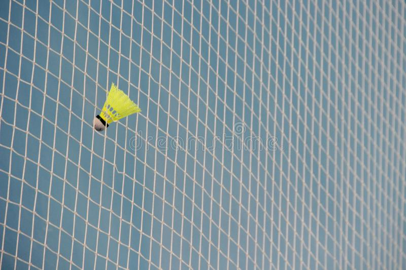 Shuttlecock in a grid badminton. Bright yellow shuttlecock in white net on blue background, badminton close-up stock photography