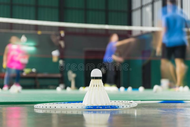 Shuttlecock resting on a badminton racket with badminton player are competiting royalty free stock photos